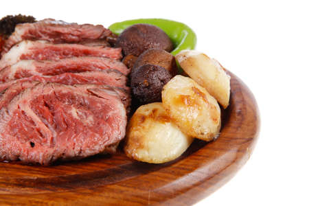 fresh grilled bbq beef meat rib eye steak on wooden plate with baked tomatoes mushroom, potatoes, hot chili pepper isolated on white backgrodun empty space for text Stock Photo