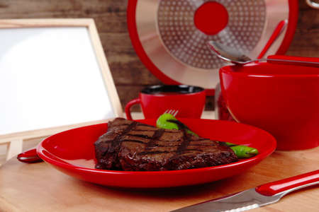 red theme lunch : fresh grilled bbq roast beef steak on red plate with green chili tomato soup ketchup sauce paprika small jug glass ground pepper american peppercorn and modern cutlery served on wooden plate over table empty nameplate menu board Stock Photo