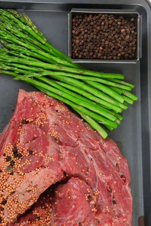 meat raw beef fillet chunk on black tray asparagus allspice isolated on white background empty space for text 스톡 콘텐츠