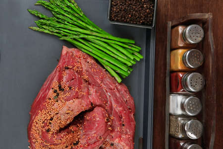 meat raw beef fillet chunk on black tray asparagus on wooden table allspice pink white black green peppercorn stainless cutlery knife fork Reklamní fotografie