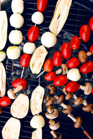 fresh raw tomatoes onion mushroom eggplant on skewers over charcoal on grid over brazier grill Stock Photo