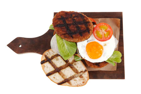 junk food big beef hamburger fried eggs on dark wood plate with modern cutlery isolated over white background Zdjęcie Seryjne