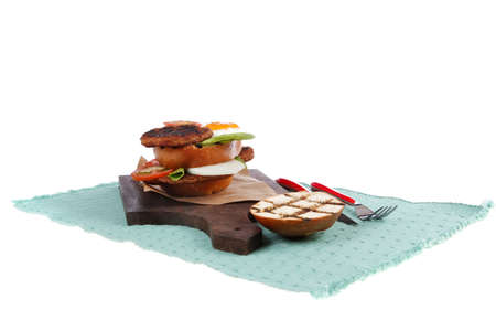 junk food big beef hamburger on dark wood plate with modern cutlery on blue mat isolated over white background Zdjęcie Seryjne