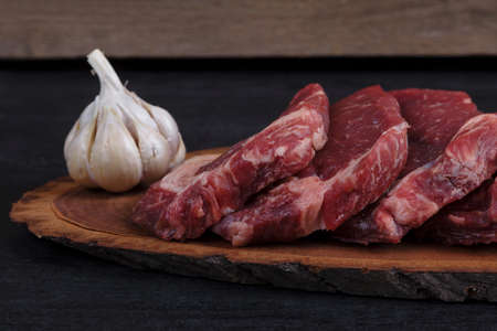 fresh raw beef pieces fillet on big size wooden plate with pepper and peppercorns in measuring spoon space for text on black background