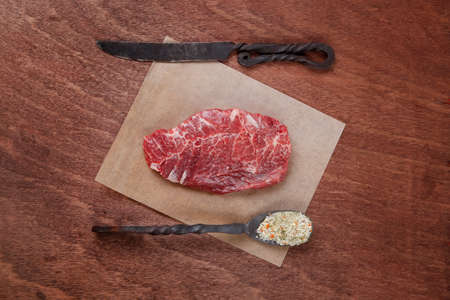 fresh raw beef rib eye steak on walnut table with salt spice and black iron antique forged cutlery fork knife empty space for text