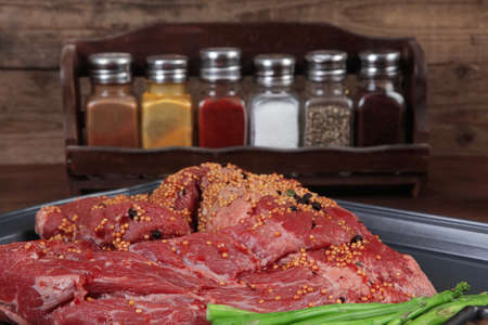 meat raw beef fillet chunk on black tray asparagus on wooden table allspice pink white black green peppercorn stainless cutlery knife fork Stock fotó