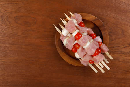 fresh raw meat fillet shish kebab turkey pork pink on skewers tomatoes mushrooms on wooden dish on big wood table