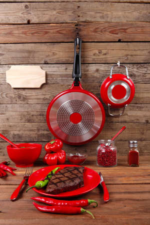red theme lunch : fresh grilled bbq roast beef steak on red plate with green chili tomato soup ketchup sauce paprika small jug glass ground pepper american peppercorn and modern cutlery served on wooden table with empty nameplate Stock fotó