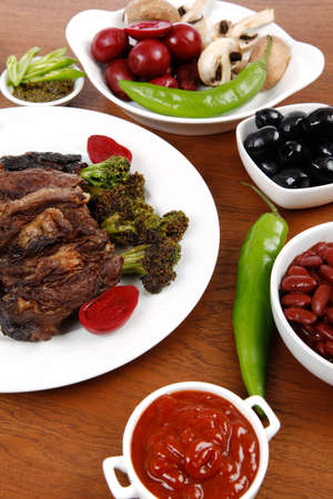 lunch of grilled meat served on big white plate with asparagus pickles tomatoes olives hot black red green pepper salt baked beans and ketchup on wooden table Stock fotó