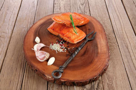 breakfast delicious portion of fresh roast salmon fillet with dry spices garlic and rosemary on wooden plate with black forged handmade fork healthy food diet cooking concept Stock fotó