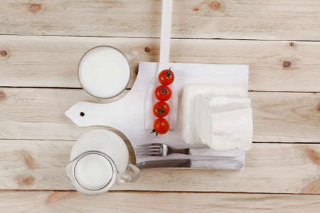 healthy dairy food fresh white greek goat sheep feta cheese on plate with milk in glass and full jug cherry tomatoes french bun over light wooden table with cutlery Stock fotó