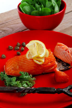 delicious portion of fresh roast salmon fillet on red plate with green salad kale tomato soup bbq sauce and black coffee over wooden table - healthy food, diet cooking concept kale tomato soup bbq sauce and black coffee over wooden table - healthy food, diet cooking concept