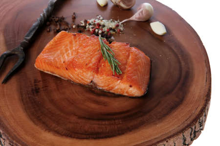 breakfast delicious portion of fresh roast salmon fillet with dry spices garlic and rosemary on wooden plate with black forged handmade fork healthy food diet cooking concept isolated on white background empty space