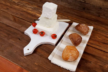 dairy healthy food fresh white greek goat sheep feta cheese on wood cutting plate with cherry tomatoes and french bun over dark wooden table