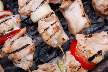 fresh turkey pink brisket shish kebab on wooden skewers with tomatoes over barbecue brazier full burned charcoal
