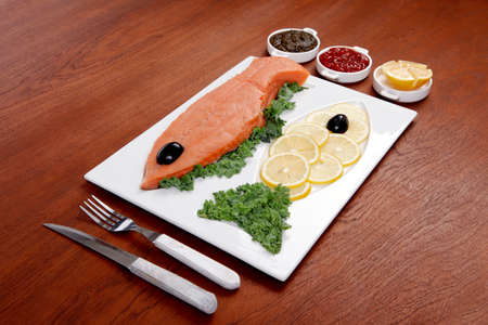healthy food fresh raw red fish with kale lemon antipesto ketchup sauce on white plate over wooden table