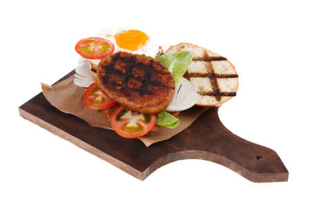 junk food big beef hamburger fried eggs on dark wood plate with modern cutlery isolated over white background Stock fotó