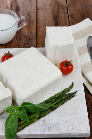 fresh white greek feta cheese with milk in jar basil cherry tomato asparagus and french bun on cutting board over dark wood table Stock fotó - 97206143