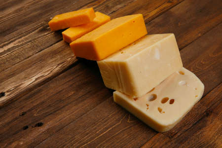 various types of fresh raw aged delicatessen cheese on wooden table cheddar edam swiss Stock fotó - 97206148