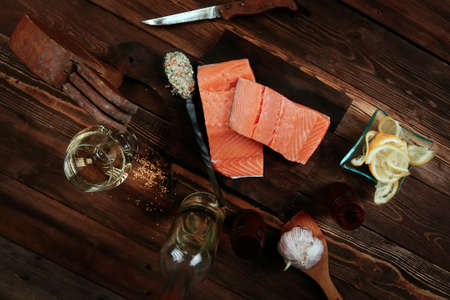 fresh raw salmon fillet served with lemon and white wine in wineglass, bottle, on dark plate over vintage wood table with handmade cutlery knife and spice on spoon Stock fotó