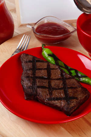 red theme lunch : fresh grilled bbq roast beef steak on red plate with green chili tomato soup ketchup sauce paprika small jug glass ground pepper american peppercorn and modern cutlery served on wooden plate over table empty nameplate menu board Stock fotó