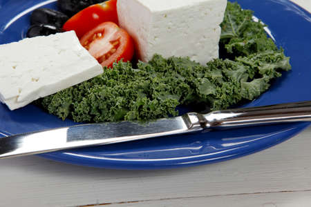 white goat feta cheese with black olives and tomatoes on blue plate over wooden table Stock fotó - 97206161