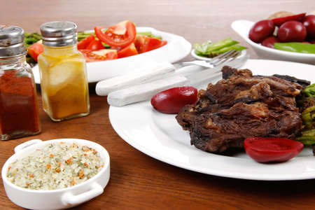 lunch of grilled meat served on big white plate with asparagus pickles tomatoes olives hot black red green pepper salt baked beans and ketchup on wooden table Stock fotó - 97206191