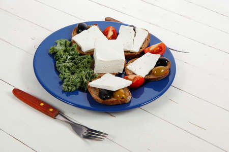 white feta greek cheese sandwich rye bread on blue plate with black spain olives tomatoes and cutlery over retro wooden table Stock fotó