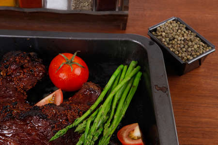 fresh glazed baked big beef meat rib chunk under sweet sauce with tomatoes hot chili pepper asparagus different peppercorn spices in black deep tray on light walnut wooden table Stock fotó - 97206449