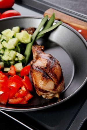 fresh hot grilled turkey drumstick leg with vegetables on black metal plate over wooden table Stock fotó - 97206476