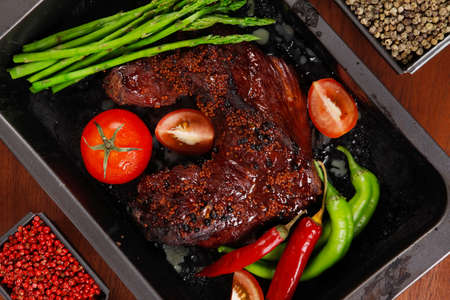 fresh glazed baked big beef meat rib chunk under sweet sauce with tomatoes hot chili pepper asparagus different peppercorn spices in black deep tray on light walnut wooden table Stock fotó - 97206479