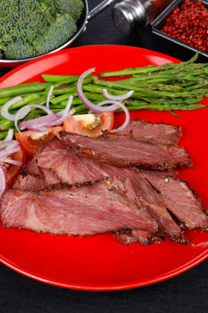fresh roast beef meat slices on red plate with paprika pink peppercorn hot chili pepper asparagus mustard powder boiled broccoli and cutlery on black wood plate