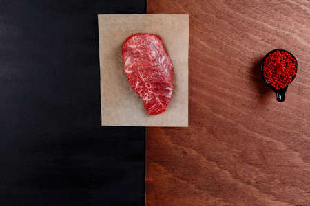 fresh raw beef rib eye steak on black walnut wooden table with red hot pepper spice in saucer Stock fotó - 97206486