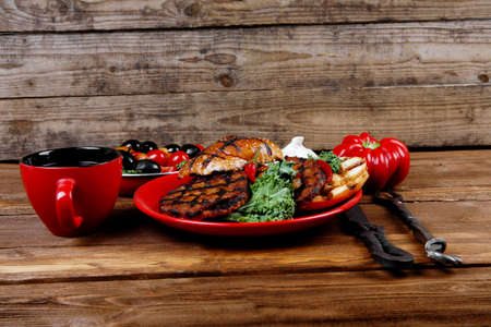 fresh grilled beef hamburger served on red plate with black coffee glass chili pepper olives green kale leaves mushroom bell garlic and forged vintage antique cutlery over wooden table empty space for text Stock fotó