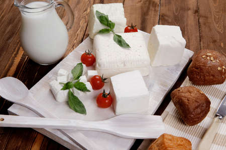 dairy food fresh white greek goat sheep feta cheese on plate with milk in pitcher cherry tomatoes french bun over dark wooden table Stock fotó - 97206492