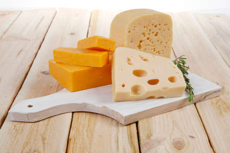 various types of fresh raw aged delicatessen cheese on white plate over light wooden table cheddar edam swiss Stock fotó