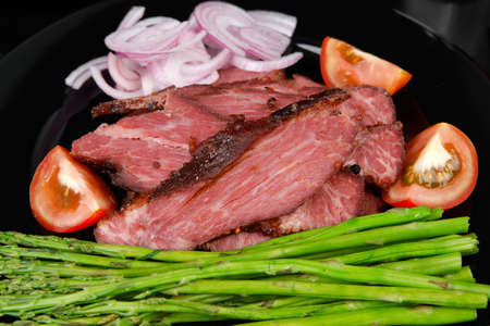business lunch fresh roast beef meat slices on black plate wotj cutlery asparagus boiled broccoli rye bun on wooden table