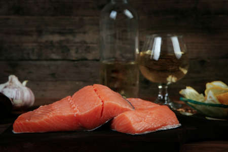 fresh raw salmon fillet served with lemon and white wine in wineglass, bottle, on dark plate over vintage wood table with handmade cutlery knife and spice on spoon with empty space background Stock fotó - 97206634