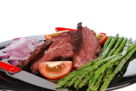 fresh sliced roast beef on black plate with cutlery and asparagus isolated on white background empty space for text Stock fotó
