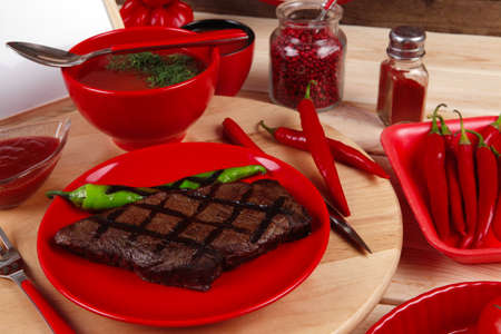 red theme lunch : fresh grilled bbq roast beef steak on red plate with green chili tomato soup ketchup sauce paprika small jug glass ground pepper american peppercorn and modern cutlery served on wooden plate over table empty nameplate menu board Stock fotó - 97206717