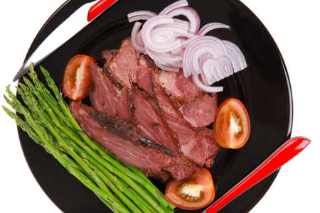fresh sliced roast beef on black plate with cutlery and asparagus isolated on white background