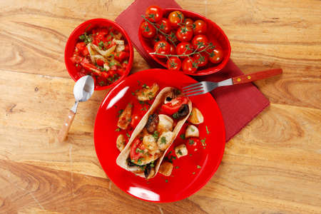 big mexican taco with tomatoes and mushroom, served with soup, fresh vegetables , on red crockery plates over wooden table with cutlery and napkin Stock fotó - 97206721