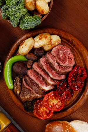 fresh roast bbq beef meat ribeye steak on wooden plate served with tomato juice in wooden cup, boiled broccoli, baked tomatoes and potatoes, with white bun, and red wine glass on light walnut wooden table Stock fotó