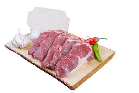 sirloin sinta fillet sliced on wooden plate with garlic and green red hot pepper isolated over white background with white empty menu plate for text near Stock fotó - 97206766