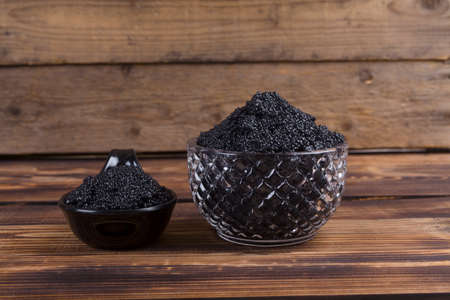 fresh raw black sturgeon hausen caviar in white crystal bowl on wooden background Stock fotó - 97206771