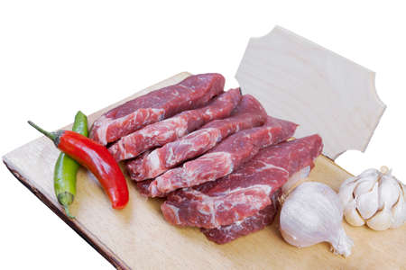 sirloin sinta fillet sliced on wooden plate with garlic and green red hot pepper isolated over white background with white empty menu plate for text near Stock fotó - 97206772