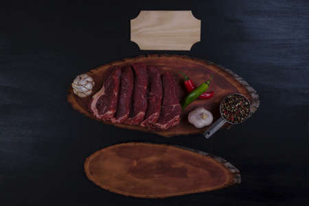 fresh raw beef pieces fillet on big size wooden plate with pepper and peppercorns in measuring spoon name plate space for text on black background Stock fotó
