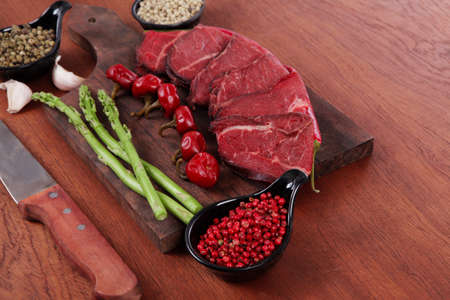 fresh beef meat asparagus greenery spices cutlery wooden table pepper crushed hot chili vegetables bowl served garlic cutting board