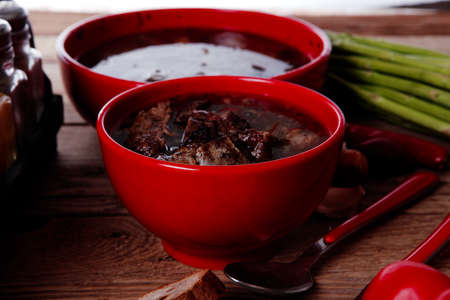 home style beef meat soup vintage country wood table asparagus pepper bell spices bread garlic cutlery spices red bowls Stock fotó - 97206783