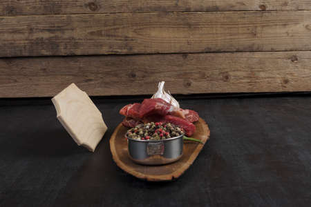 fresh raw beef piece fillet on middle size wooden plate with pepper and peppercorns in measuring spoon with name plate space for text on black background